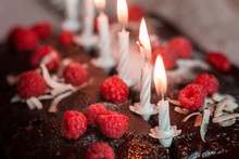 Tasty Homemade Chocolate Birthday Cake Decorated Of Some Raspberries And Candles Served On The Gentle Pink Background