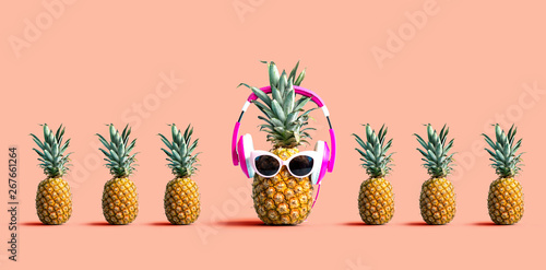 One out unique pineapple wearing headphones on a solid color background - 267661264