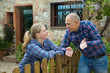 Leinwandbild Motiv Man and woman communicate in a friendly way on the border of their farms