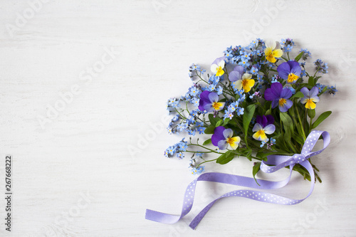 Valokuva A bouquet of forget-me-nots and pansies on a wooden background