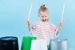 Leinwandbild Motiv Little jolly boy using drumsticks on iron and plastic buckets. Playing rhythm.
