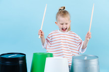 Little Jolly Boy Using Drumsticks On Iron And Plastic Buckets. Playing Rhythm.