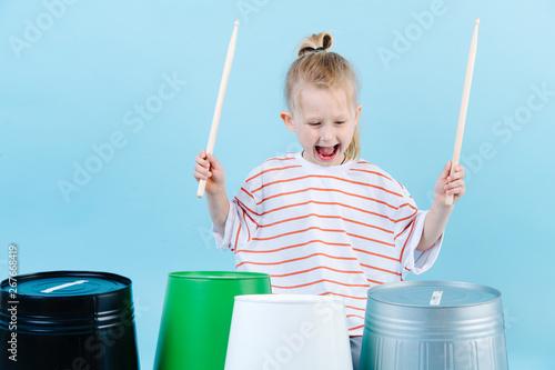Fotografia Little jolly boy using drumsticks on iron and plastic buckets