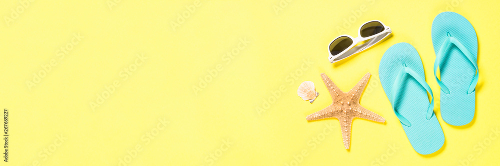 Fototapety, obrazy: Blue flip flops, swimsuit, sunglasses and starfish on yellow background.
