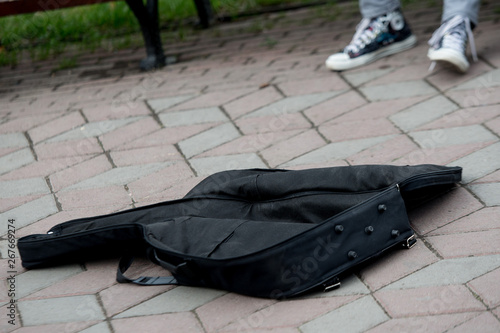 Photo ase for guitar with money and coins on the street