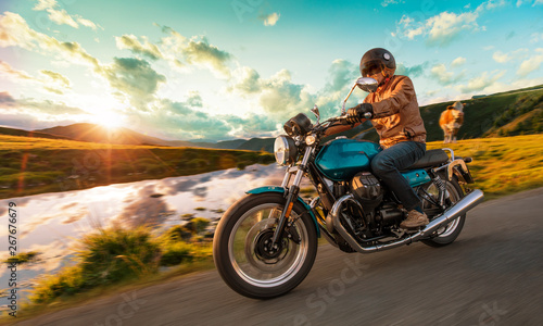 Photo Motorcycle driver riding in Alpine highway, Nockalmstrasse, Austria, central Europe