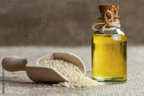 Valokuva Glass bottle of sesame oil and raw sesame seeds in wooden shovel or spoon on burlap sack
