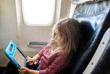 A Toddler Aged Girl Using A Tablet Device On A Airplane.