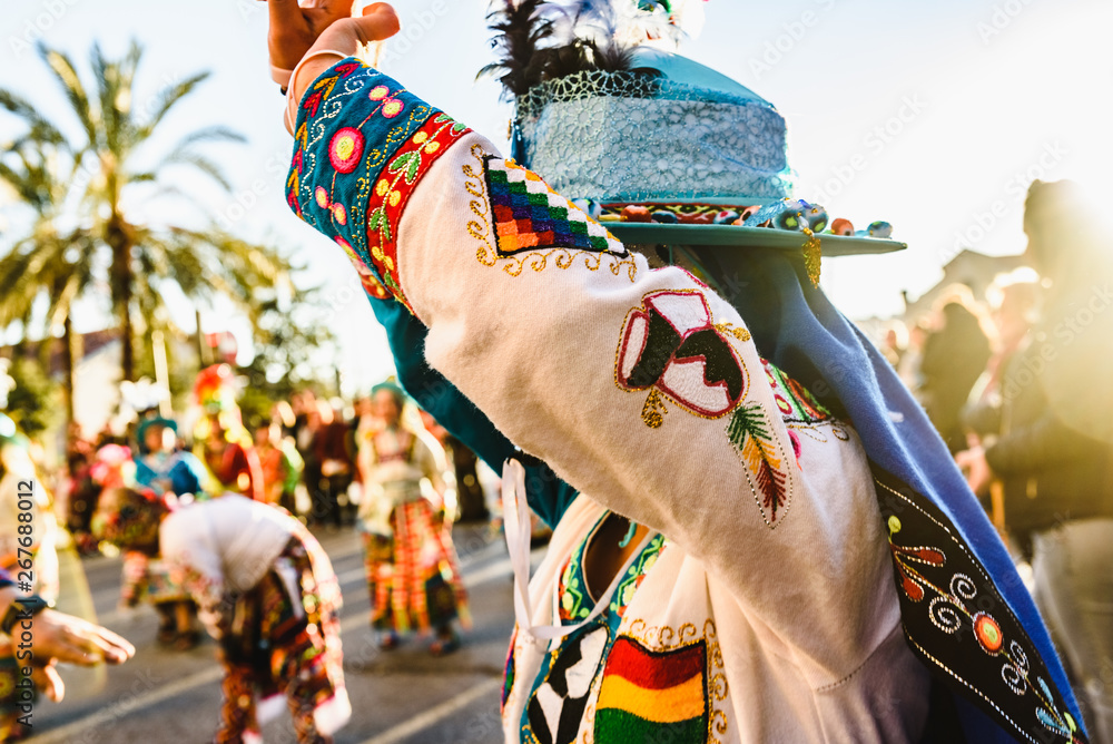 Fototapeta Valencia, Spain - February 16, 2019: Woman performing the Bolivian folk dance the Tinku dressed in folkloric and colorful traditional dress during the carnival of the Ruzafa district in Valencia.