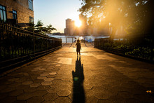 A Toddler Aged Girl Standing On The Brooklyn Waterfront At Sunset.