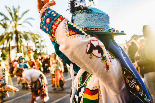 Valencia, Spain - February 16, 2019: Woman performing the Bolivian folk dance the Tinku dressed in folkloric and colorful traditional dress during the carnival of the Ruzafa district in Valencia. - 267688012