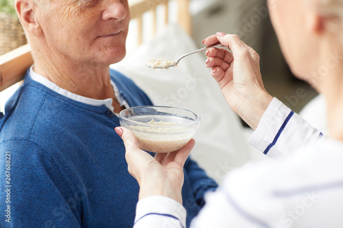 Side view closeup of senior woman feeding husband lying on bed in recovery, copy Canvas Print