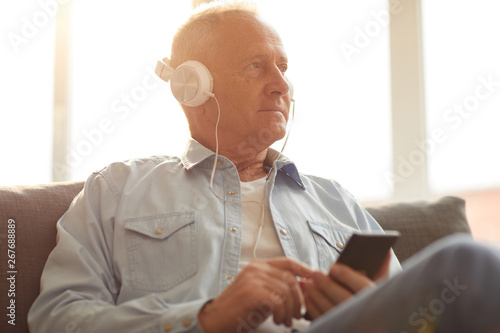 Foto  Portrait of modern senior man wearing headphones using smartphone sitting on sof
