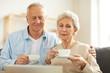 Leinwandbild Motiv Warm toned portrait of modern senior couple drinking tea while watching videos via laptop, copy space
