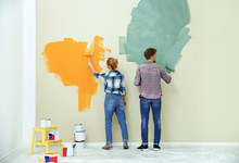 Young Couple Painting Wall Ind...