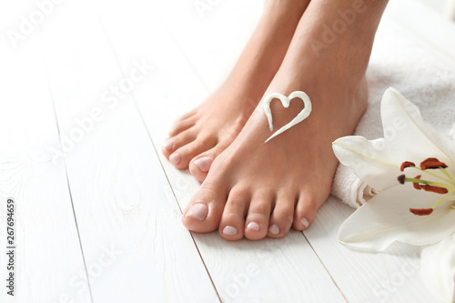 Woman with beautiful feet, cream, flower and towel on white wooden floor, space for text. Spa treatment