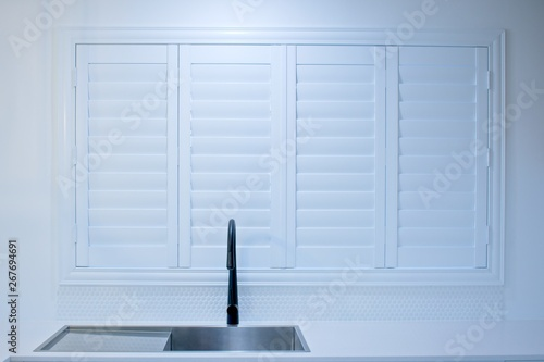 Obraz na płótnie Closed plantation shutters and black kitchen sink mixer tap.