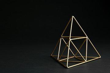 Shiny decorative gold pyramid on black background. Space for text
