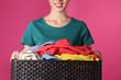 Leinwandbild Motiv Young woman holding basket with clothes on color background, closeup