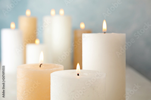 Fotografie, Obraz  Burning candles on table against color background, closeup