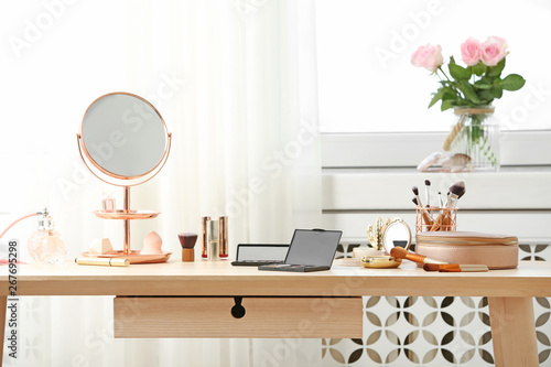 Photo Dressing table with different makeup products and accessories in room interior