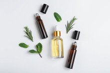 Little Bottles Of Essential Oils With Different Herbs On White Background, Top View