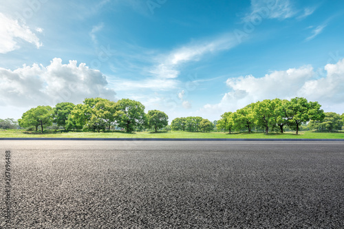 Fotobehang Blauw Country road and green forest natural landscape under the blue sky