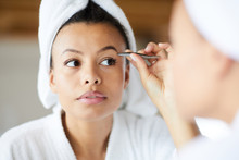 Head And Shoulders Portrait Of  Beautiful Mixed-Race Woman Plucking Eyebrows Looking In Mirror During Morning Routine, Copy Space