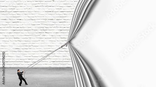 Businessman pulling down blank white curtain covering white brick wall and gray concrete floor background Canvas Print