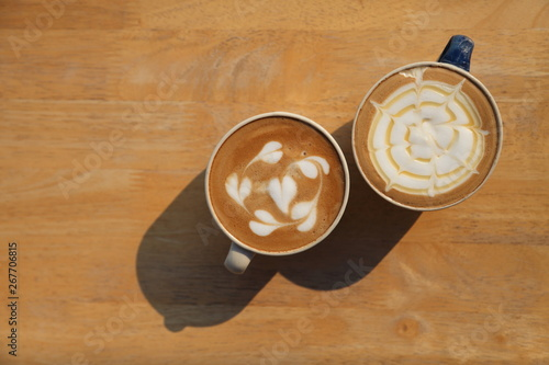 Foto op Plexiglas Chocolade Two cup of different coffee which are cappuccino and caramel latte milk on the wooden rustic table in the morning with strong light and shadow with copy space
