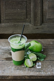 Green apple smoothie in glass and kale leaves on wooden table - 267712621