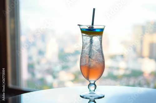 Colorful ice cocktail decorated with fruits on glass table near large window with cityscape view as background
