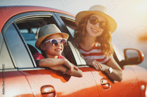 fototapeta na lodówkę happy family mother and child girl goes to summer travel trip in car.