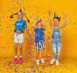 canvas print picture - happy children on holidays  jumping in multicolored confetti on yellow
