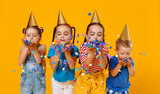 happy children on holidays  jumping in multicolored confetti on yellow - 267717046