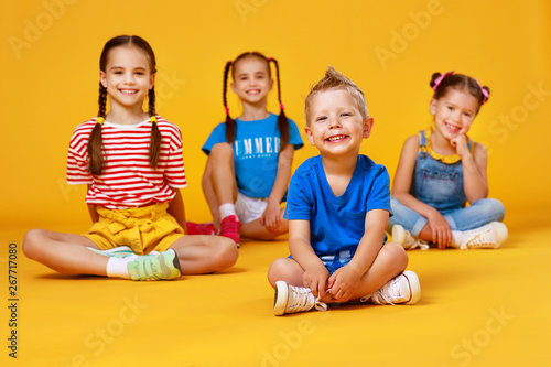 Fotografiet  group of cheerful happy children on colored yellow background.