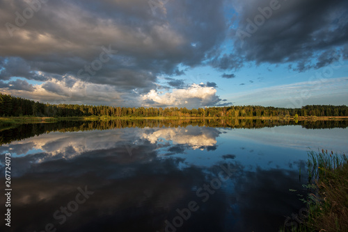 Photo Stands Kiev beautiful sunset by the lake with green grass meadow and white clouds in the blue sky