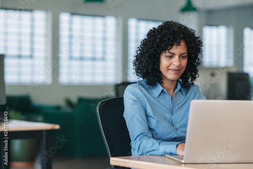 fototapeta na drzwi i meble Smiling businesswoman sitting at her desk working on a laptop