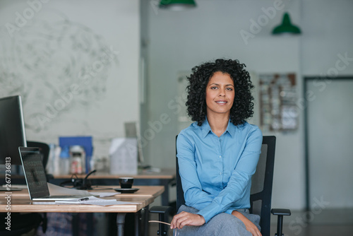 Photo  Smiling young businesswoman sitting at her desk in an office