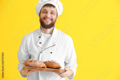 Fotografie, Obraz Young baker with fresh bread on color background