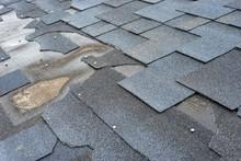 Сlose Up View Of Bitumen Shingles Roof Damage That Needs Repair.