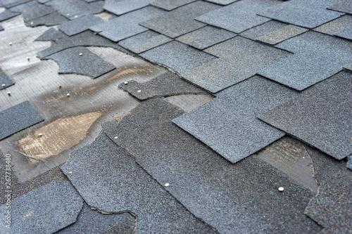 Fototapeta Сlose up view of bitumen shingles roof damage that needs repair.