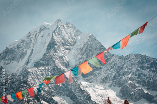 Staande foto Nepal Everest trekking and hiking. Mountains of Nepal. Mountain in focus. Nepalese prayer flags are blurred. Adventure in the Himalayas