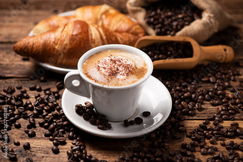 A cup of cappuccino with coffee bean as background. - 267761288