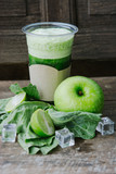 Green apple smoothie in glass and kale leaves on wooden table - 267762676