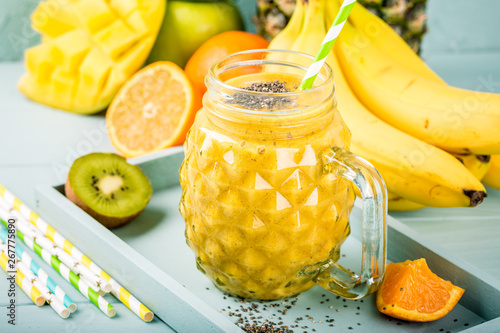 Photo  Exotic summer food concept with tropical fruits banana, orange, mango, pineapple, kiwi and yellow smoothie juice with chia seeds in glass