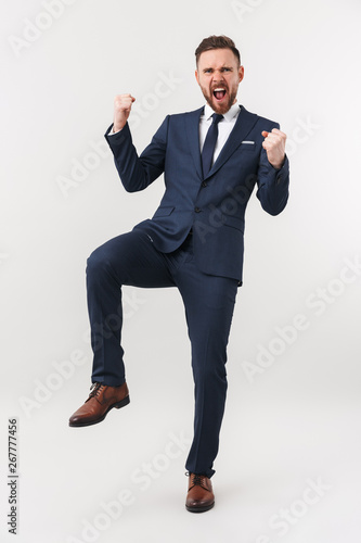 Excited businessman posing isolated over white wall background make winner gesture.