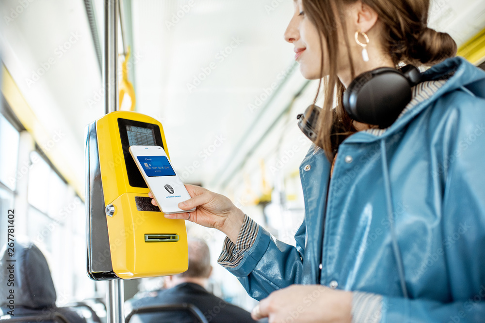 Fototapeta Woman paying conctactless with smartphone for the public transport in the tram