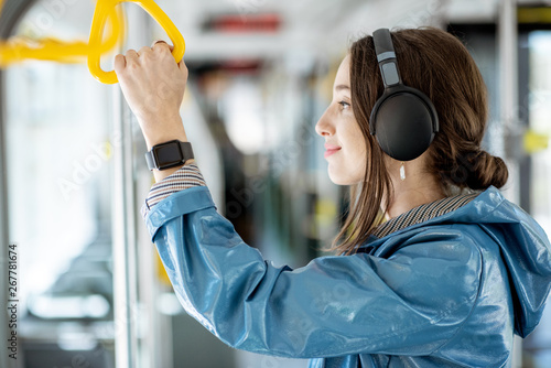 Young woman holding handle while moving in the modern tram. Happy passenger enjoying trip at the public transport - 267781674