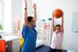 Leinwandbild Motiv Upset hard-working boy sitting in medical cabinet and raising basketball ball